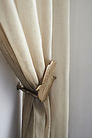A neutral curtain is held back by a brass tie back in the shape of a hand