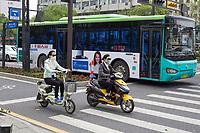 Suzhou, Jiangsu, China.  Young Women on Electric Motorbikes Wearing Breathing Masks.