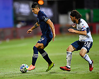 LAKE BUENA VISTA, FL - JULY 26: Alan Pulido of Sporting KC is pressured by Russell Teibert of Vancouver Whitecaps FC during a game between Vancouver Whitecaps and Sporting Kansas City at ESPN Wide World of Sports on July 26, 2020 in Lake Buena Vista, Florida.
