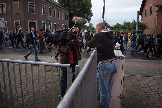 Wilkommensfest fuer Fluechtlinge im saechsichen Heidenau.<br /> Nachdem Polizei und politisch Verantwortliche vergeblich versucht hatten ein Wilkommensfest fuer Fluechtlinge mit dem Argument des Polizeilichen Notstands zu verbieten feierten hunderte Menschen zusammen. Fuer die Fluechtlinge waren Kleidungs- und Sachspenden nach Heidenau gebracht worden, die in Berlin, Dresden und anderswo gesammelt wurden.<br /> Zahlreiche Polizeikraefte waren zum Schutz des Festes im Einsatz.<br /> Im Bild: Ein Fernsehteam interviewt einen Anwohner zu seiner Meinung ueber die Fluechtlinge, waehrend im Hintergrund die Fluechtlingsunterstuetzer mit einer Demonstration zum Bahnhof ziehen um nach Hause zu fahren.<br /> 28.8.2015, Heidenau<br /> Copyright: Christian-Ditsch.de<br /> [Inhaltsveraendernde Manipulation des Fotos nur nach ausdruecklicher Genehmigung des Fotografen. Vereinbarungen ueber Abtretung von Persoenlichkeitsrechten/Model Release der abgebildeten Person/Personen liegen nicht vor. NO MODEL RELEASE! Nur fuer Redaktionelle Zwecke. Don't publish without copyright Christian-Ditsch.de, Veroeffentlichung nur mit Fotografennennung, sowie gegen Honorar, MwSt. und Beleg. Konto: I N G - D i B a, IBAN DE58500105175400192269, BIC INGDDEFFXXX, Kontakt: post@christian-ditsch.de<br /> Bei der Bearbeitung der Dateiinformationen darf die Urheberkennzeichnung in den EXIF- und  IPTC-Daten nicht entfernt werden, diese sind in digitalen Medien nach §95c UrhG rechtlich geschuetzt. Der Urhebervermerk wird gemaess §13 UrhG verlangt.]