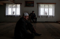 BULGARIA, Arda, April 15, 2011. Bulgarian muslim men sit in a mosque in the remote village of Arda in the Rhodope Mountains, southern Bulgaria. Bulgarian Muslims, which today are nearly 8% of the country's population and the largest muslim minority community in the European Union, revived their cultural and religious traditions after the fall of communist regime in Bulgaria in 1989. .BULGARIE, Arda, 15 Avril 2011. Des Bulgares de confession musulmane sont assis dans la mosquée du petit village de Arda dans les montagnes des Rhodopes en Bulgarie. La minorité musulmane qui représente aujourd'hui près de 8% de la population totale du pays et qui est la plus large majorité musulmane dans les pays de l'Union Européenne a ravive ses traditions culturelles et religieuse après la chute du régime communiste Bulgare en 1989.