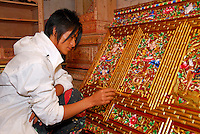 Tibetan artist hand-paints intricately carved animal and floral motifs on traditional storage cabinet, Barkhor, Lhasa, Tibet.