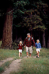 Dad & two daughters hiking trail at forest's edge, Moraine Park, Rocky Mtn Nat'l Park, CO
