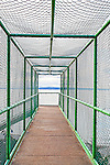 Overpass walkway caged or enclosed in chain link fencing.  At Carkeek Park, Seattle, this walkway overpass crossed train tracks to allow beach access.