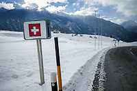 Switzerland. Canton Graubünden. Alvaneu. A road sign with the swiss flag. The flag of Switzerland displays a white cross in the centre of a square red field. The white cross is known as the Swiss cross. Snow on the fields and on the Alps mountains. Asphalt Road. Alvaneu is part of the municipality Albula/Alvr. 26.12.2020 © 2020 Didier Ruef
