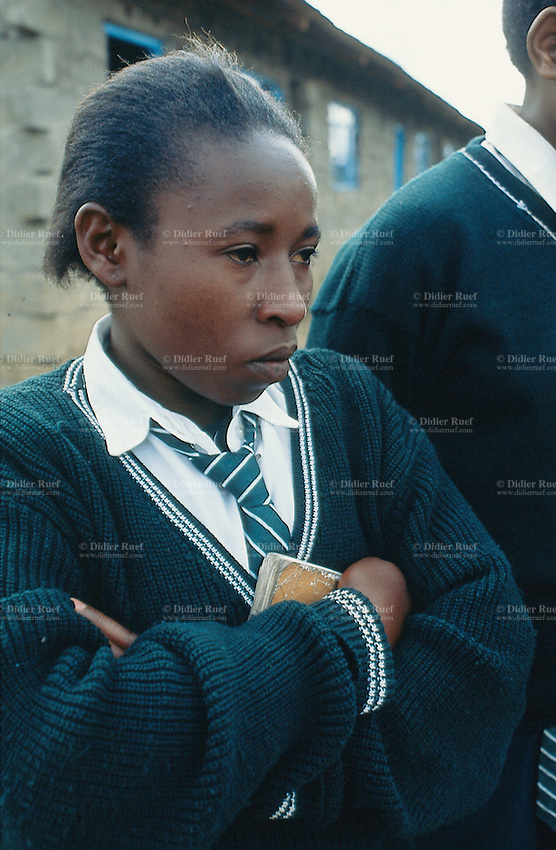 Kenya. Rift Valley Province. Nyahururu. Munyaka secondary school. Students stay on line in the early morning. A girl girl is wearing a green uniform and a tie. © 2004 Didier Ruef