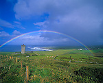County Clare, Ireland<br /> Rainbow arches over tower castle and fields near Doolin, on the west coast of Ireland