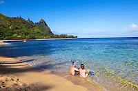 Newlyweds with snorkeling gear sit in the gentle surf at Tunnels Beach, with Mt. Makana (or Bali Hai) in the distance, Kaua'i.