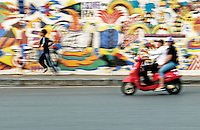 Traffic buzzes past the colorful 3.85 km long Hanoi Ceramic Mosaic Mural. It is the world's largest ceramic mosaic built from ceramic tesserae.<br />