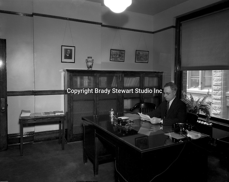 Pittsburgh PA: Administrator reading documents in hid office at Duquesne University.<br />