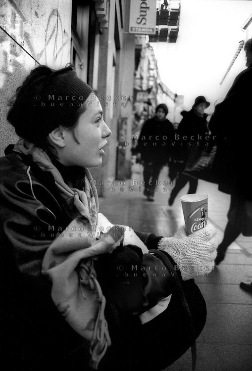 milano, una giovane ragazza fa elemosina con un piccolo cane in via torino, strada di shopping in centro città --- milan, a young girl beggar with a little dog in torino street, a shopping street in downtown