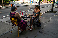 NEW YORK, NEW YORK - JUNE 18: People share drinks on a table set at the sidewalk at Hells Kitchen area as city prepares for reopening on June 18, 2020 in New York City. New York City is preparing to enter phase 2 of reopening where restaurants and bars can offer outdoor dining this coming Monday. (Photo by Eduardo MunozAlvarez/VIEWpress)