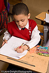 K-8 Parochial School Bronx New York Grade 1 language arts male student at work on multiple choice worksheet vertical