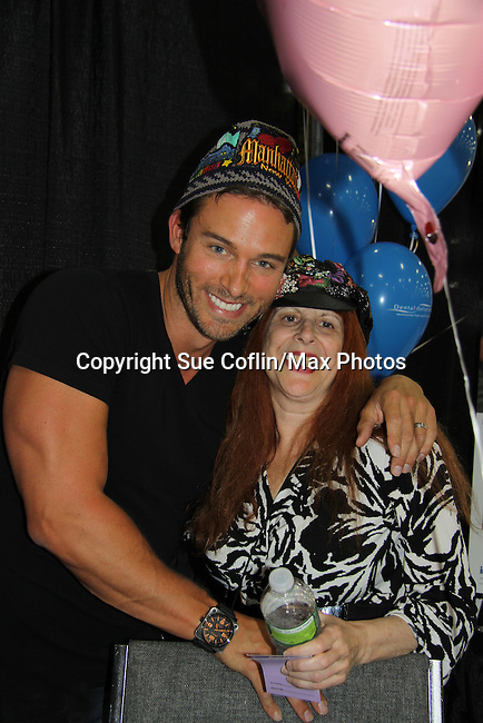 Days of Our Lives Eric Martsolf poses with Jane Elissa who wears one of her Hats for Health at the 8th Annual Connecticut Women's Expo presented by Comcast on September 11 & 12, 2010 at the Connecticut Expo Center, Hartford, Connecticut. (Photo by Sue Coflin/Max Photos)