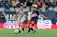 FOXBOROUGH, MA - JULY 7: Mark Delgado #8 of Toronto FC brings the ball forward as Carles Gil #22 of New England Revolution defends during a game between Toronto FC and New England Revolution at Gillette Stadium on July 7, 2021 in Foxborough, Massachusetts.