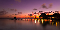 Colorful twilight on lit-up pier with thatched roofs reflecting on the lagoon, in Rangiroa Tuamotus atoll, French Polynesia, South Pacific Ocean
