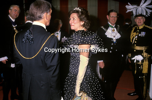 City of London. 1990's<br /> In a black polka dot dress with short puff sleeves and long white kid gloves; crowned with a diamond tiera Mrs Carolyn Graham, the Lady Mayoress makes small talk with city peacock plummed and gold chained businessmen after a banquet at the Guildhall.