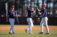 (L-R) Mike Marcinko (2), Ryan McMillen (10), and Jimmy Spanos (13) celebrate their win over the Belmont Abbey Crusaders at Abbey Yard on February 8, 2015 in Belmont, North Carolina.  The Raiders defeated the Crusaders 14-0.  (Brian Westerholt/Four Seam Images)