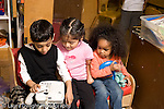 Education preschoool children ages 3-5 group of two girls and a boy in dressup dress playing in kitchen family area interacting horizontal