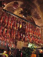 Prosciutto hams hang under a Roman arch