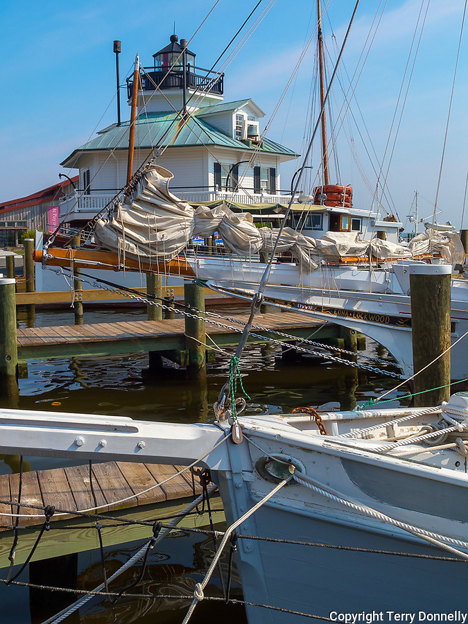 Chesapeake Bay Maritime Museum, St. Michaels, Maryland<br /> Hooper Strait Lighthouse (1879) stands behind the bows and rigging of tow historic fishing boats