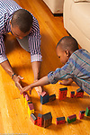 4 year old boy playing with wooden building blocks and vehicles building town or street with father's help
