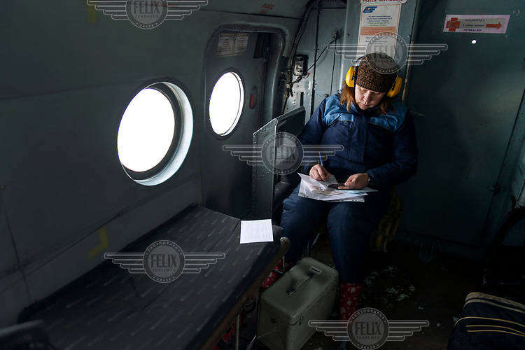 Anna, a medic, fills out documents during a helicopter flight from Vankor to Turukhansk.