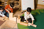 Education Preschool 3-5 year olds block area three boys building long construction together horizontal