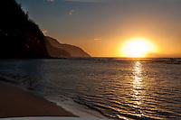 The setting sun casting a warm glow over the cliffs of Na Pali and the Pacific ocean off Ke'e Beach, Kauai.