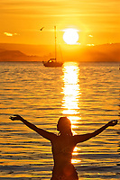 Pictured: Natasha Jenkins in the sea during sunrise as seen through the RNLI boat station in Mumbles, near Swansea, Wales, UK. Sunday 13 June 2021<br /> Re: High temperatures and sunshine has been forecast for most of the UK.