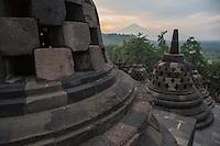 Borobudur, Java, Indonesia.  Stupas and Mount Merapi in Early-morning Haze.  The diamond-shaped holes symbolize the passions that still linger as men rise toward Nirvana.  The square-shaped holes symbolize the passions that have left without a trace  as men rise toward Nirvana.