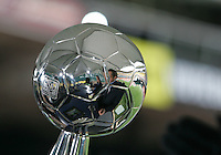 ESPN broadcasters Julie Foudy and Rob Stone reflected in the Alan I. Rothenberg trophy. The Houston Dynamo defeated the New England Revolution 2-1 in the finals of the MLS Cup at RFK Memorial Stadium in Washington, D. C., on November 18, 2007.