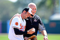 Baltimore Orioles legend Cal Ripken Jr. greets J.J. Hardy #2 after throwing out the ceremonial first pitch before a Spring Training game against the Toronto Blue Jays at Ed Smith Stadium on March 7, 2013 in Sarasota, Florida.  Balitmore defeated Toronto 11-10.  (Mike Janes/Four Seam Images)