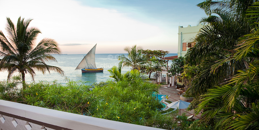 Stone Town, Zanzibar, Tanzania.  A dhow passes Shangani Point, Stone Town's westernmost tip, en route to Dar  es Salaam in late afternoon.   View from a Serena Inn balcony.