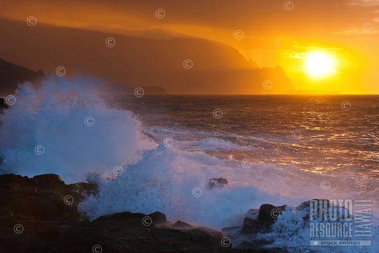 Waves crash against Kauai's north shore as a rain shower casts a curtain over the setting sun.