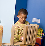Educaton preschool 4-5 year olds boy standing building with blocks lining up large long wooden blocks on top of structure concentrating intent