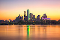 """""""Dallas Skyline at Sunrise"""" – Gleaming like a sparkling gem, the early morning sun envelops the Dallas skyline in incandescent warmth with colors of aureolin, saffron, lavender, wisteria, and marigold. In the foreground, a flooded Trinity River winds past the city, revealing a rarely photographed moment of the beautiful Dallas skyline. (Photo/Stephen A. Masker)"""