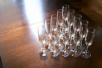 Flute champagne sparkling wine glasses on a wooden table empty waiting to be filled. The O'Farrell Restaurant, Acassuso, Buenos Aires Argentina, South America