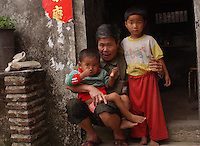 Chen Zi Huang, 58, and Qi Qi, 3, male and Gwen Gwen, 5, female eat rice and fish. The children are kept in a cage in a village house belonging to their uncle. The children's parents are both in prison and the uncle is too poor to afford child care for the children and are afraid they may be stolen a common problem in China...PHOTO BY SINOPIX
