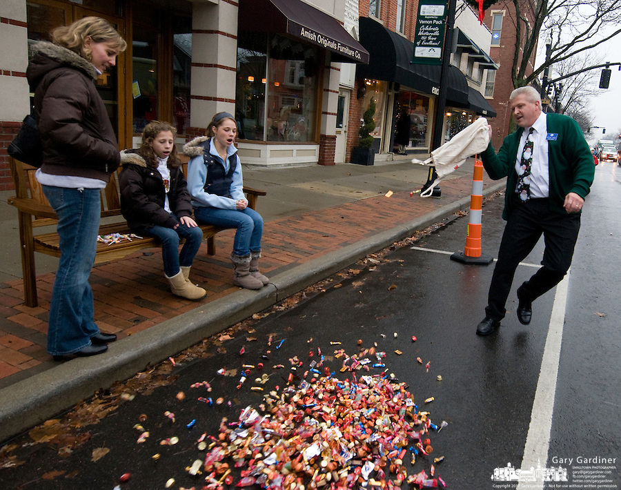 A large bag of candy  is dumped at the feet of three Christmas parade watchers in downtown Westerville, Ohio, on a wet, rainy afternoon. The bag of candy, offered by a grocery store manager, was intended to feed more children but the weather brought a much smaller crowd than expected with the result being more candy for fewer people. Photo Copyright Gary Gardiner. Not for reproduction without written permission.