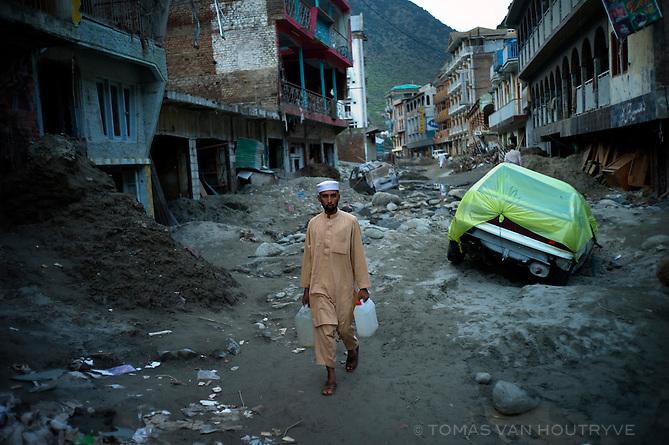 Man carrying water walks down the flood damaged main street of Bahrain in the Swat valley, Pakistan, on Aug. 27, 2010. Flood waters reached 3-4 stories high in the buildings left standing. Other buildings were completely swept away.