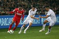 SWANSEA, WALES - MARCH 16: Jack Cork of Swansea (C) challenges Raheem Sterling of Liverpool (L)<br /> Re: Premier League match between Swansea City and Liverpool at the Liberty Stadium on March 16, 2015 in Swansea, Wales
