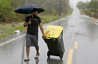 Omar Mejia, a resident in a nearby neighborhood, removes a trash can Wednesday, April 28, 2021, that had been washed onto W. Monroe Avenue in Lowell because of flash flooding. The National Weather Service office in Tulsa said the storm system that began moving through Northwest Arkansas Tuesday night had dropped from 1 to 3 inches of rain across the area by mid-morning Wednesday. With rainfall of 4 to 6 inches being reported in some areas. Check out nwaonline.com/210429Daily/ and nwadg.com/photos for a photo gallery.<br />(NWA Democrat-Gazette/David Gottschalk)