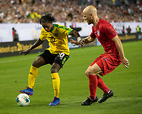 NASHVILLE, TN - JULY 4: Darren Mattocks #10 attacks with Michael Bradley #4 defending during a game between Jamaica and USMNT at Nissan Stadium on July 4, 2019 in Nashville, Tennessee.