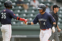 Second baseman Everlouis Lozada (4) of the Greenville Drive is greeted by Kervin Suarez after scoring a run in Game 1 of a doubleheader against the Hickory Crawdads on Wednesday, July 25, 2018, at Fluor Field at the West End in Greenville, South Carolina. Greenville won, 4-1. (Tom Priddy/Four Seam Images)
