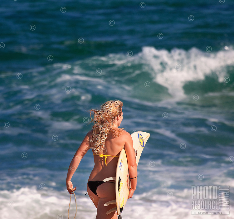 Young surfer ready for her surfing session.