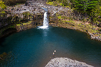 A couple goes for a swim at a waterfall near Hilo, Big Island of Hawai'i.