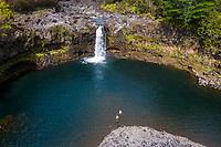 A couple goes for a swim at a waterfall near Hilo, Big Island of Hawai'i.
