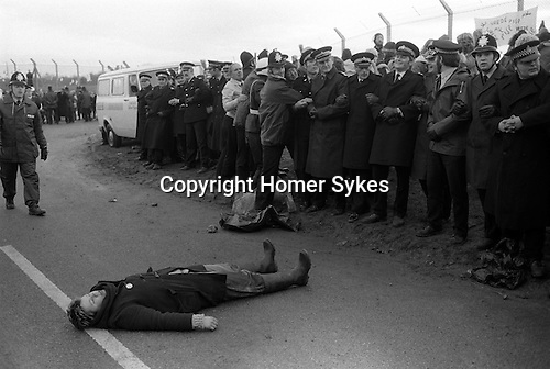 """For much of the 1980s, """"women's peace camps"""" were established in protest at the deployment of cruise missiles. They came to be known as """"The Greenham Women"""" or """"peace women"""", and their 19-year protest drew worldwide media and public attention, often due to the peace women cutting through the fences of the base. A lone protestor makes a stand by breaking through the police cordon and peacefully prostrated herself in the middle of the road. She was very quickly removed. 1983"""