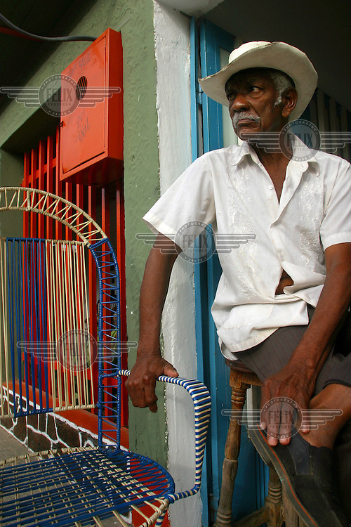 Sitting in the doorway of a coffee shop, an old man watches people pass by on the street.